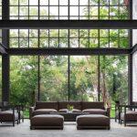 Industriële ruimte met stalen zwarte binten een vide en grote hoge ramen met uitzicht op groene tuin