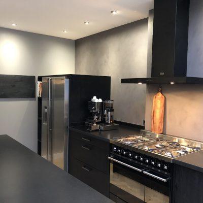 Industriele houtskool zwarte keuken met beton cire achterwand in antraciet