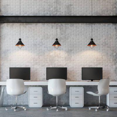 Kantoor plek industrieel met zwart stelen binten en vintage lampen. Het bureau is wit met 3 werkplekken en draaifauteuils