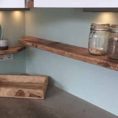 Houten wandplanken boven betonen werkblad in keuken