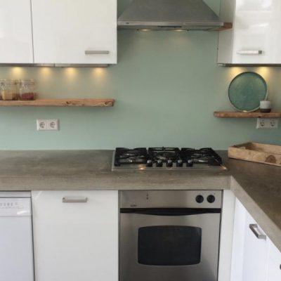 Betonnen werkblad in witte keuken met hout accenten