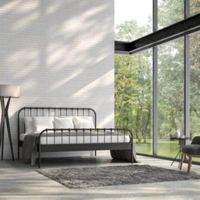 Vintage grijze muur met hoge zwarte stalen kozijnen en stalen bedframe uitzicht op groene tuin
